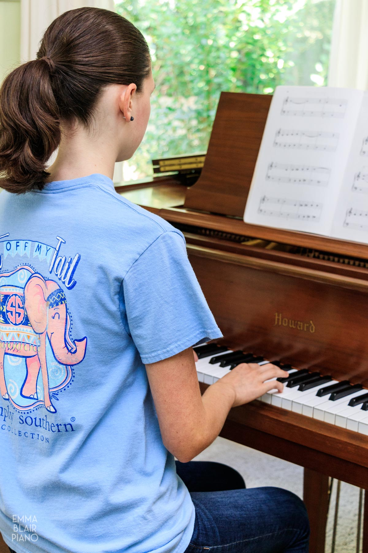 teenage girl playing a beginning piano piece on a brown piano