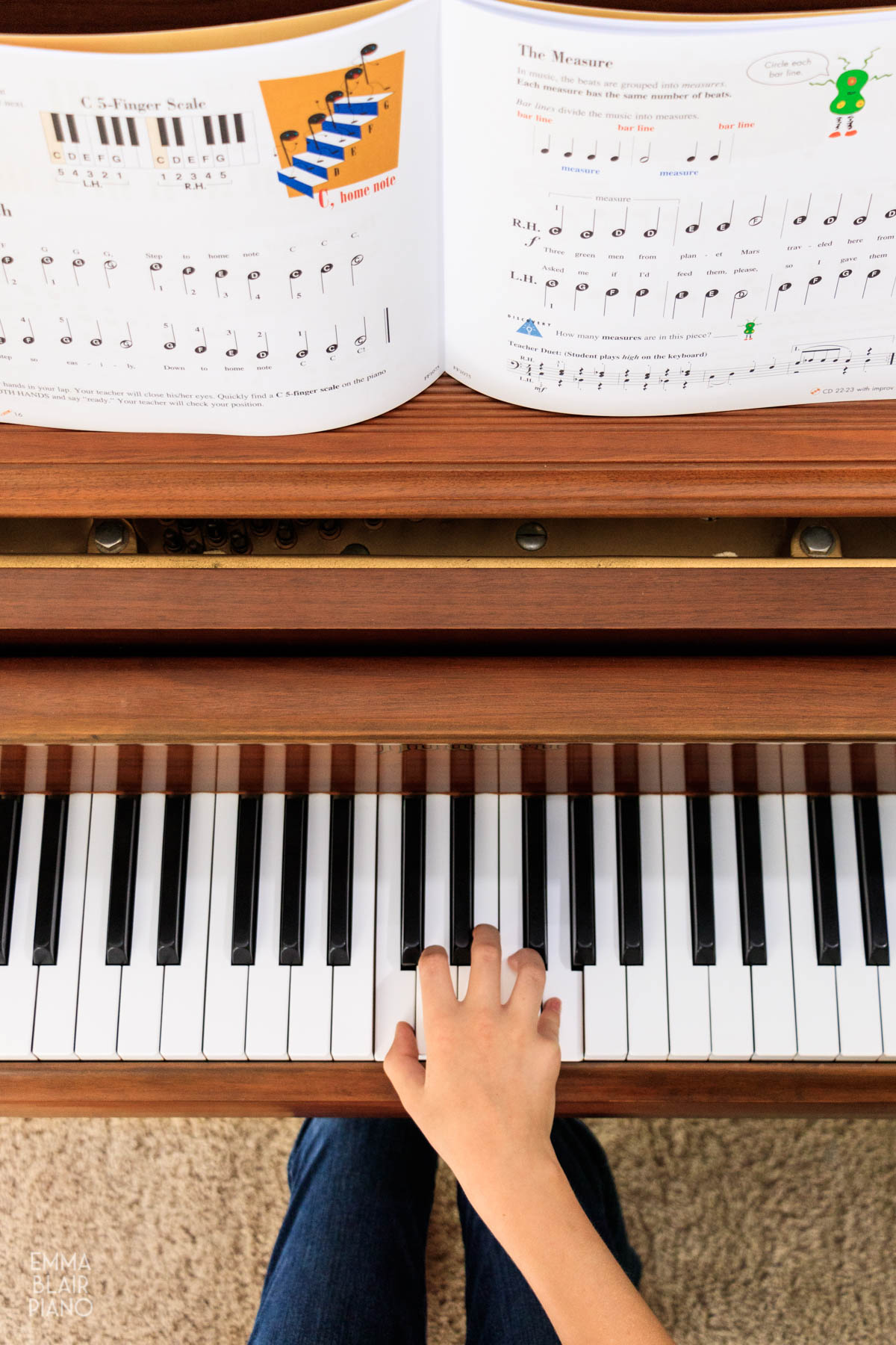 young piano student playing from Faber Piano Adventures primer book