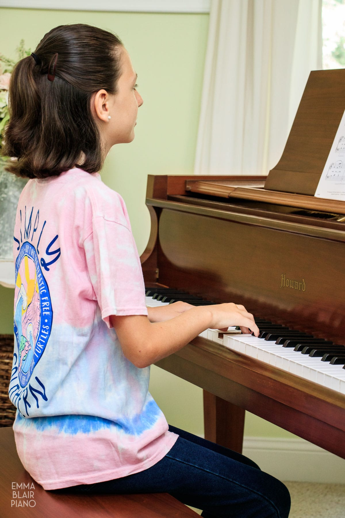 young girl playing a brown grand piano