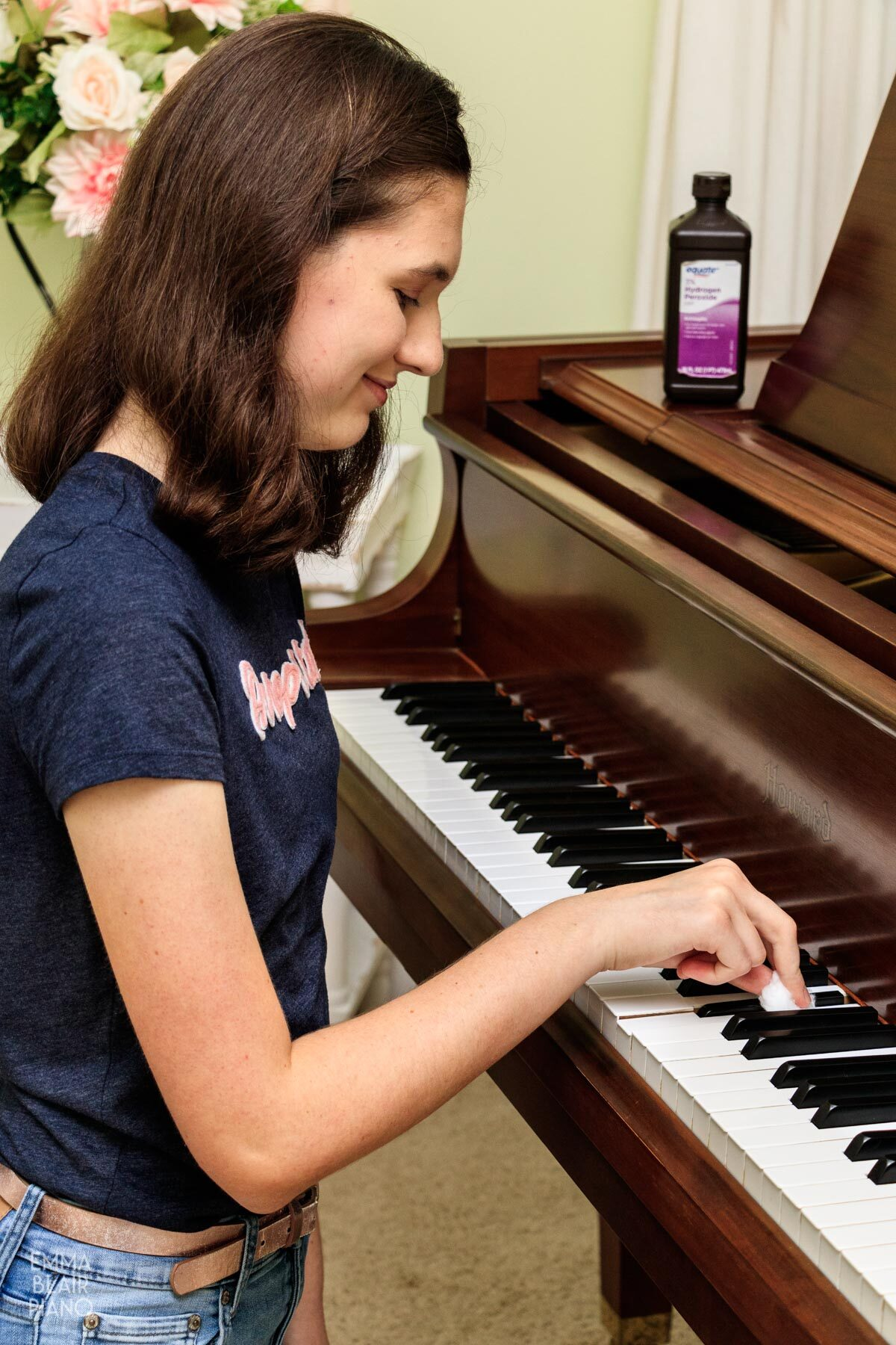 girl cleaning piano keys with hydrogen peroxide on a cotton ball