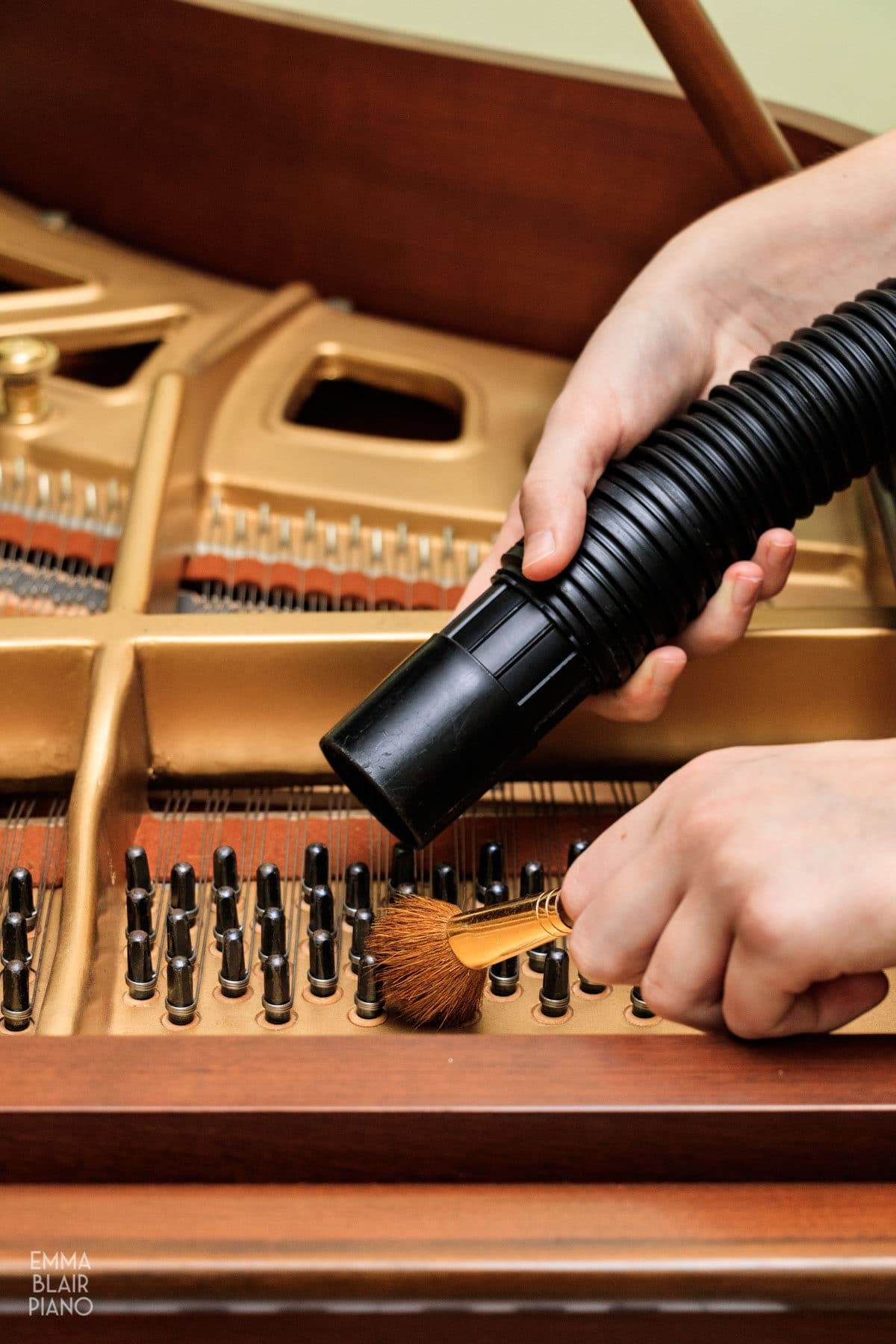 girl brushing and vacuuming dust off of piano tuning pegs