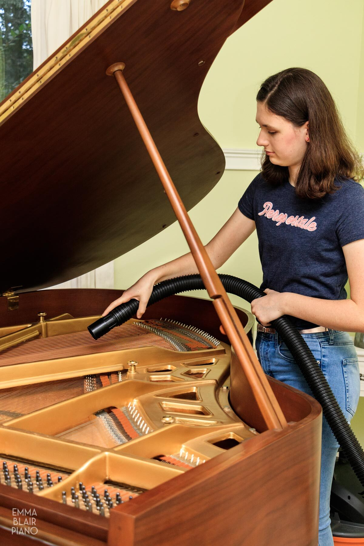 girl blowing dust out of the soundboard of a grand piano