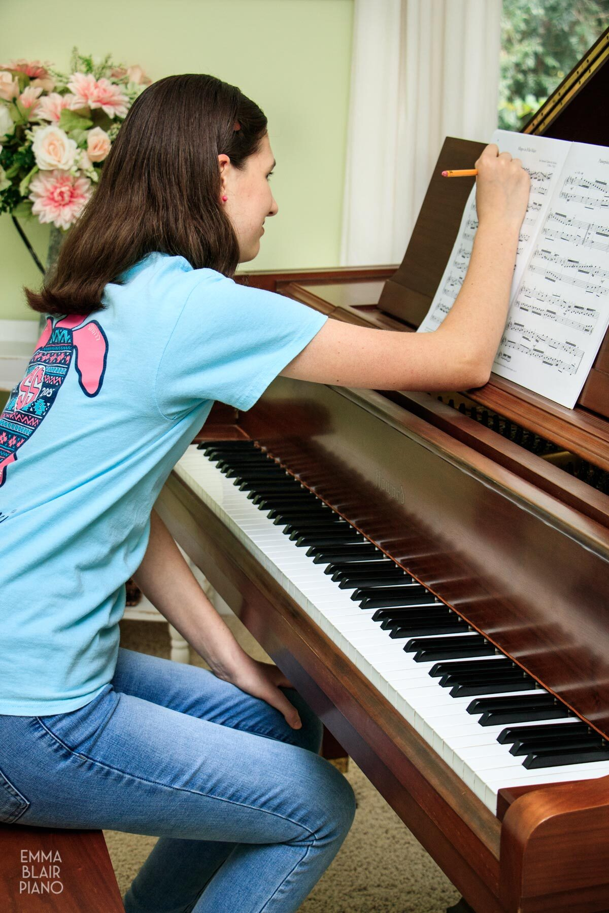 girl making notes on sheet music for a classical piece