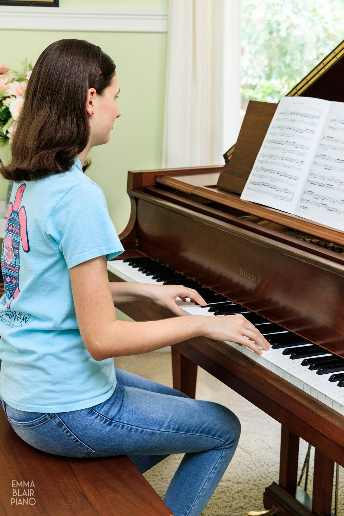 girl playing a classical piano piece with the sheet music
