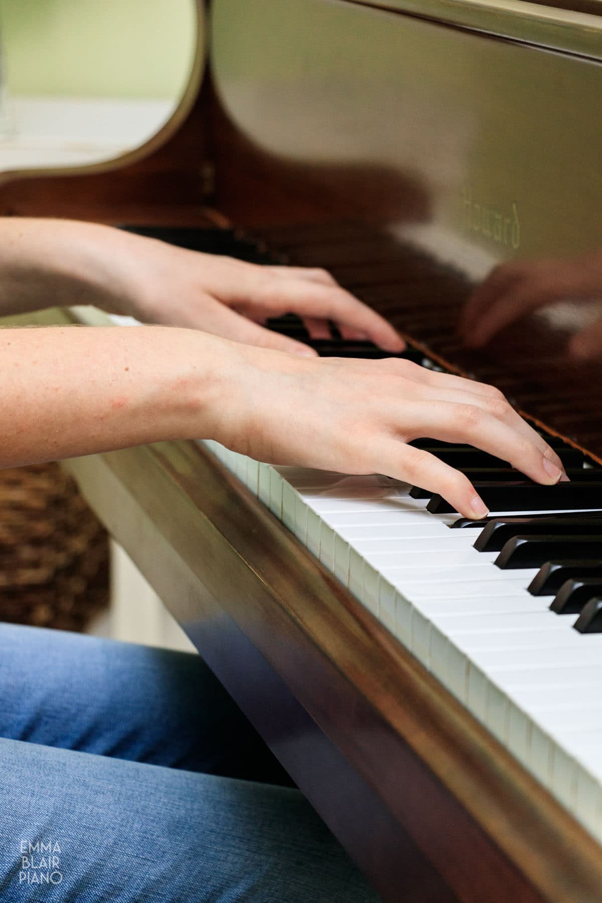 closeup of a teenage girl's hands as she plays the piano