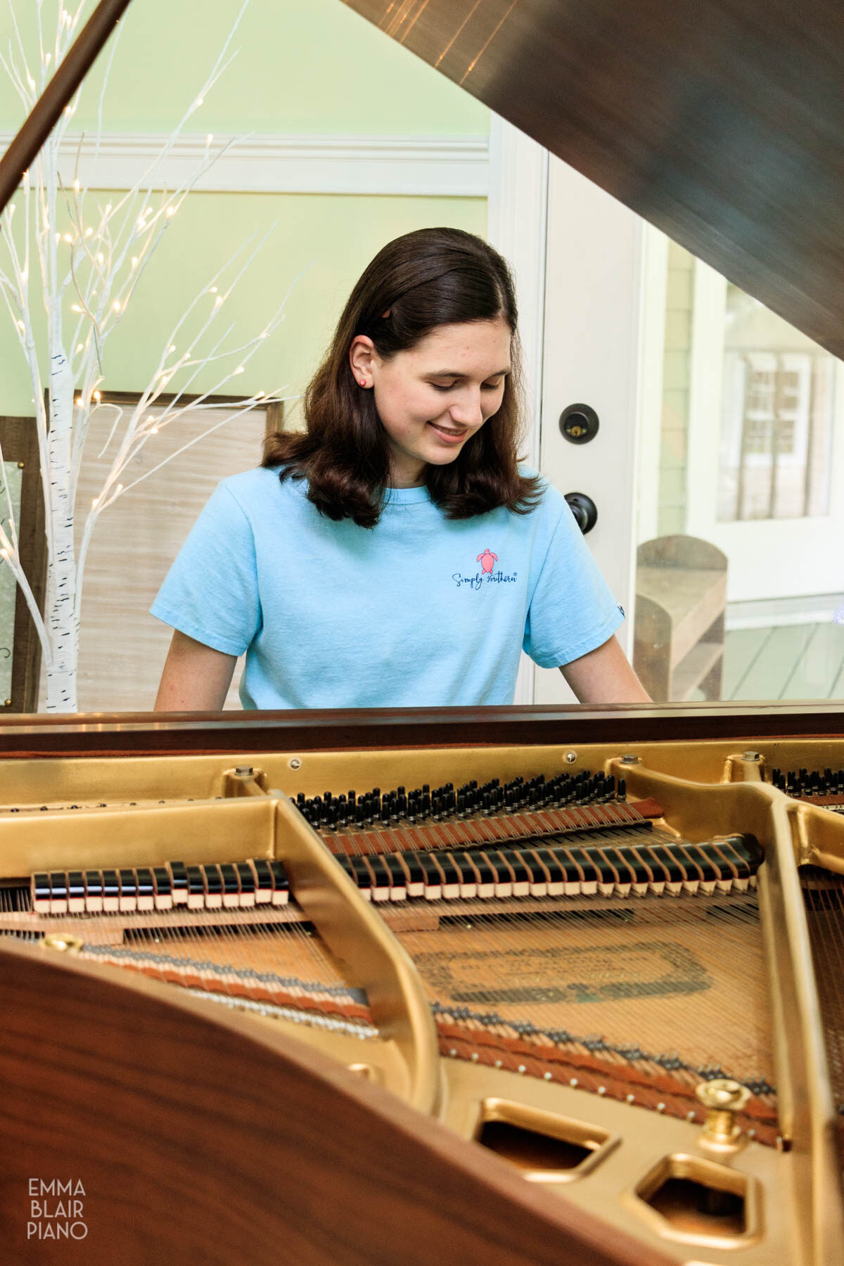 teenage girl smiling as she plays a piano song from memory